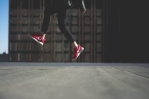 Human in Black Track Pants With Red Nike Sneakers Jumping