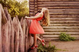 Woman in Orange Sleeveless Flare Dress Standing in Front of Wooden Fence