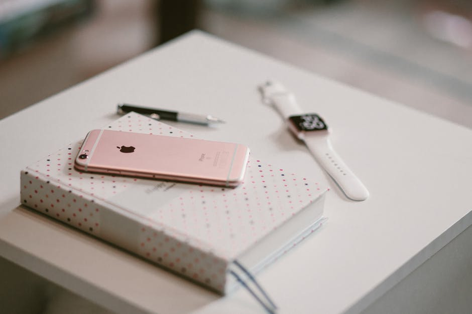 Rose Gold Iphone 6 S On Top Of White Covered Book Wallpaper Hd